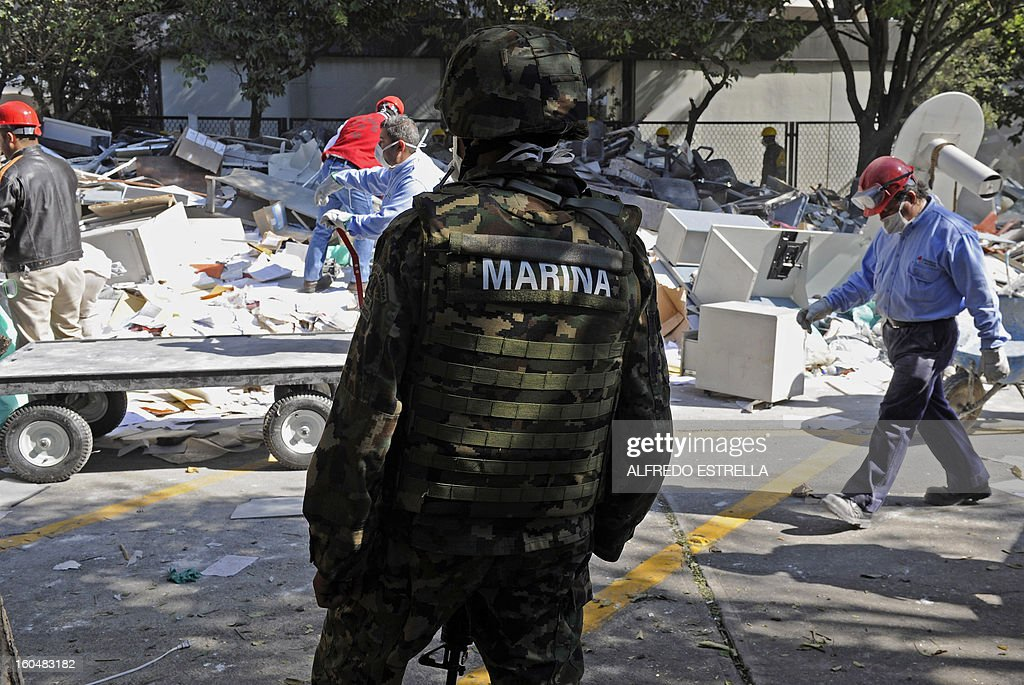 A Mexican Navy soldier stands guard inside the premises of the building that houses the state-owned Mexican oil giant Pemex, following a blast on the eve, in Mexico City on February 01, 2013. An explosion rocked the skyscraper, leaving up to 32 dead and 121 injured. Hundreds of firefighters, police and soldiers toiled through the night after the blast ripped through an annex of the 54-floor tower leaving concrete, computers and office furniture strewn on the ground. AFP PHOTO/Alredo Estrella