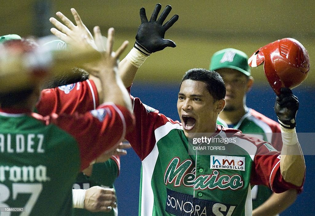 Mexican Oscar Robles celebrates with teammates after scored and tiees the game at the top of the eighth inning of the Caribbean Baseball Series game...