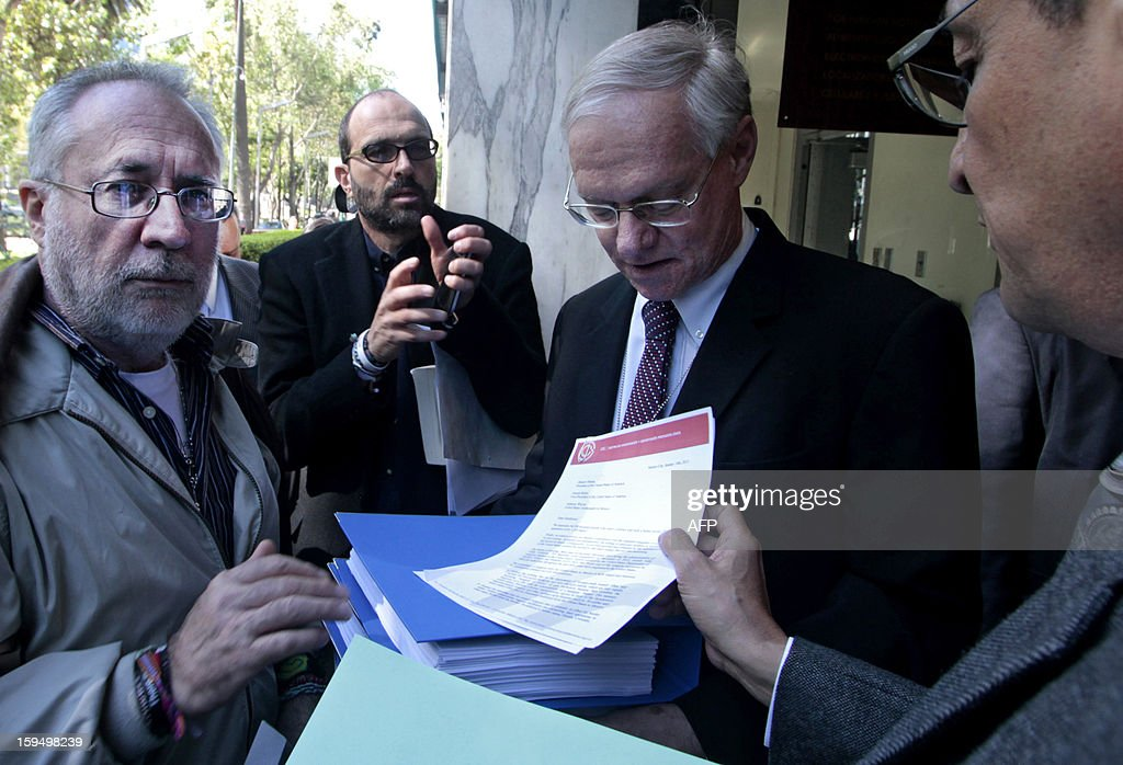 Mexican peace activists Javier Sicilia (L) and Sergio Aguayo (R) hand to US official Michael Glover (2-R), documents signed by 54.558 citizens in support of the ban on the importation of weapons in Mexico, at the embassy of the United States in Mexico City on January 14, 2013. AFP PHOTO / Pedro Pardo