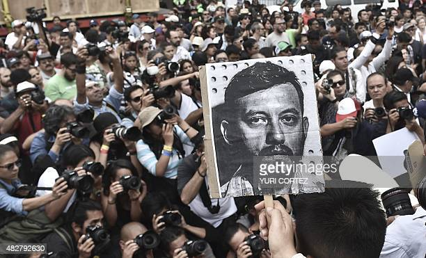 Mexican photojournalists hold pictures of their murdered colleague Ruben Espinosa during a demonstration held at the Angel of Independence square in...