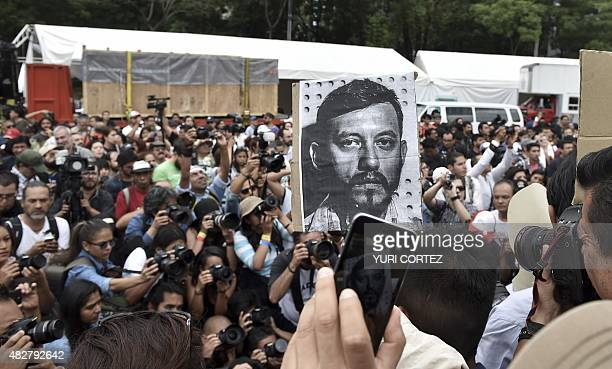 Mexican photojournalists hold pictures of their murdered colleague Ruben Espinosa during a demontration held at the Angel of Independence square in...