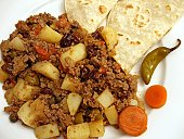 Photo of Mexican dish called Picadillo served with tortillas and garnished with chile and carrot slices.  Picadillo is made with ground beef, potatoes, tomatoes, raisins, olives and onions.  Spice is