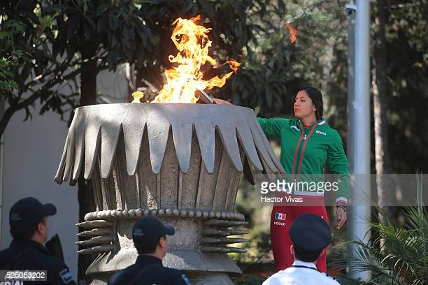 Mexican pole vaulter Carmen Correa lights the Olympic Torch during a ceremony to stand out the 100 Days to Rio 2016 Olympic Games at Centro Deportivo...