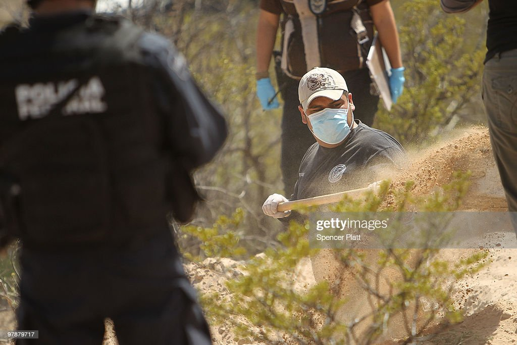 Mexican police and forensic workers dig at a site believed to hold the remains of numerous victims of recent drug violence on March 19, 2010 in the county ofJuarez, Mexico. The border city of Juarez has been racked by violent drug-related crime, making it among the most dangerous cities in the world. As competing drug cartels fight over lucrative drug corridors along the U.S. border, the murder rate in Juarez has risen to 173 slayings for every 100,000 residents. President Felipe Calderon in 2009 disbanded the corrupt local police force and sent 10,000 soldiers to Juarez, but the violence has raged on. With a population of 1.3 million in Juarez, 2,600 died in drug-related violence last year and 500 so far this year, including two Americans who worked for the U.S. Consulate last weekend as they returned from a children�s party.