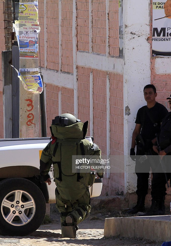 A Mexican Police bomb squad member heads to defuse a grenade found at a crime scene in Hostotipaquillo, Jalisco State, Mexico on January 29, 2013. An unidentified armed command killed three people, including the police director of the municipality Hostotipaquillo, Lucio Rosales Astorga. AFP PHOTO/Hector Guerrero