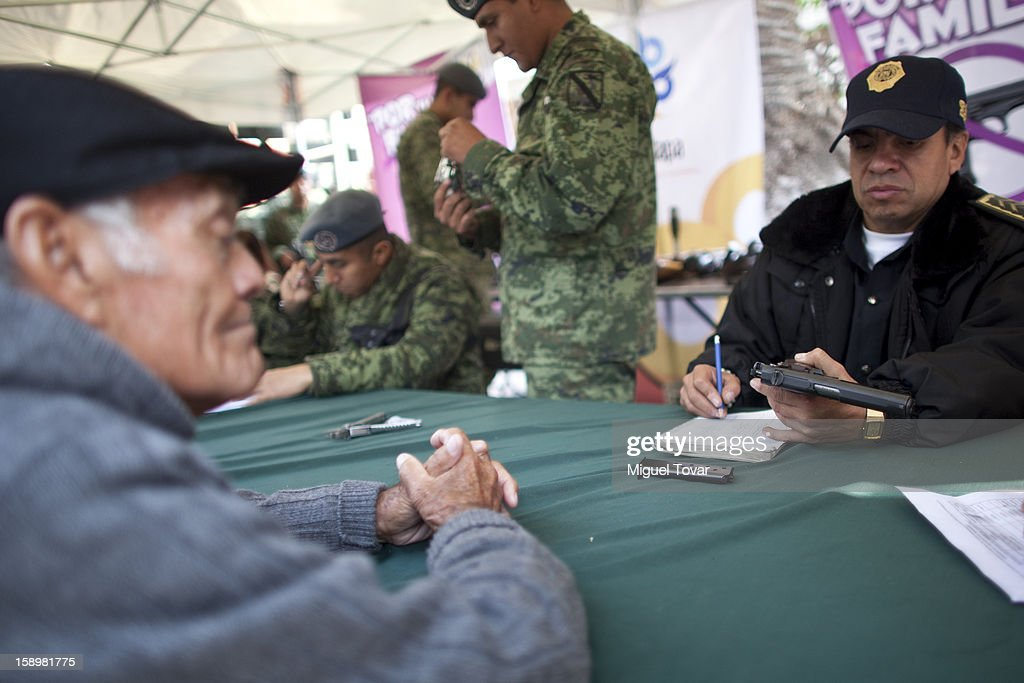 A mexican police officer examines a weapon after being exchanged by its owner on January 04, 2013 in Mexico City, Mexico. More than a thousand weapons have been changed for a tablet, bicycles or money in a low-income neighborhood in the capital, according to authorities.