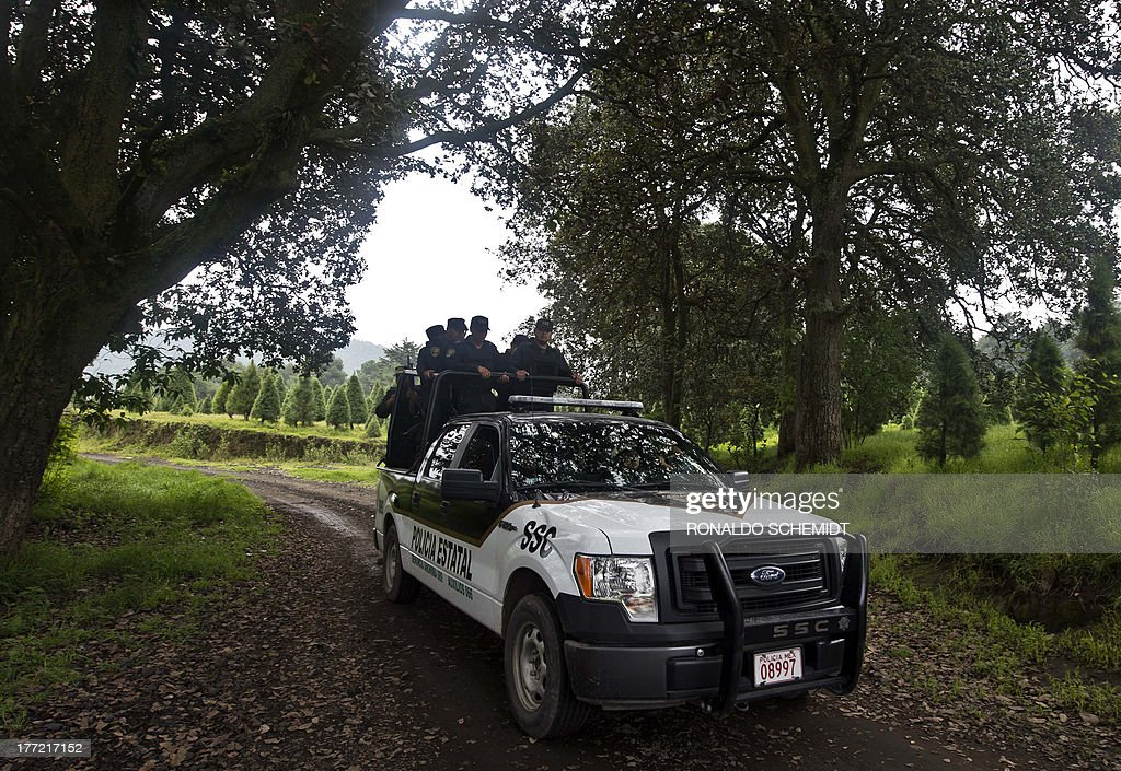 Mexican police officers are seen patrolling rural tracks near a park in the municipality of Tlalmanalco, some 30 km southeast of Mexico City on August 22, 2013, where at least 7 bodies were discovered in a mass grave. Mexican authorities dug up the muddy mass grave and were investigating Thursday if the remains belong to 12 young people whose kidnapping in May shocked the capital. Mexico City's top prosecutor, Rodolfo Rios, said the remains of seven people have been recovered since the search began in a park on Wednesday and that workers are still digging for more bodies. The victims were kidnapped from a downtown bar in broad daylight on a Sunday morning three months ago in a case that raised concerns about security in Mexico City, which has been relatively immune from the country's drug cartel violence.
