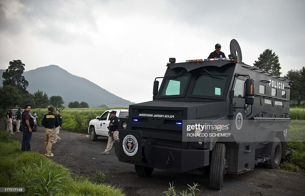 Mexican police officers block a road leading to a park in the municipality of Tlalmanalco, some 30 km southeast of Mexico City on August 22, 2013, where at least 7 bodies were discovered in a mass grave. Mexican authorities dug up the muddy mass grave and were investigating Thursday if the remains belong to 12 young people whose kidnapping in May shocked the capital. Mexico City's top prosecutor, Rodolfo Rios, said the remains of seven people have been recovered since the search began in a park on Wednesday and that workers are still digging for more bodies. The victims were kidnapped from a downtown bar in broad daylight on a Sunday morning three months ago in a case that raised concerns about security in Mexico City, which has been relatively immune from the country's drug cartel violence.