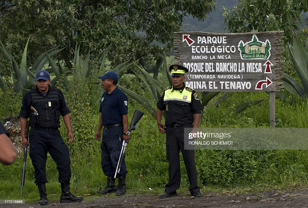 Mexican police officers stand guard on August 22, 2013 at an entrance of a park in the municipality of Tlalmanalco, some 30 km southeast of Mexico City, where at least 7 bodies were discovered in a mass grave. Mexican authorities dug up the muddy mass grave and were investigating Thursday if the remains belong to 12 young people whose kidnapping in May shocked the capital. Mexico City's top prosecutor, Rodolfo Rios, said the remains of seven people have been recovered since the search began in a park on Wednesday and that workers are still digging for more bodies. The victims were kidnapped from a downtown bar in broad daylight on a Sunday morning three months ago in a case that raised concerns about security in Mexico City, which has been relatively immune from the country's drug cartel violence.