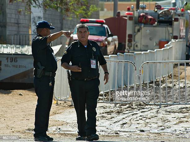 Mexican police officers talk near the back of the building where 35 children died in a fire in a daycare in Hermosillo Sonora state Mexico on June 6...