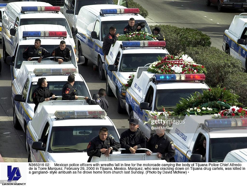 Mexican police officers with wreaths fall in line for the motorcade carrying the body of Tijuana Police Chief Alfredo de la Torre Marquez February 29...
