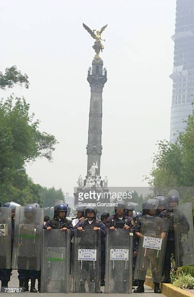 Mexican police stand guard during a celebration around the Angel of Independence monument June 13 2002 in Mexico City Approximately one hundred...