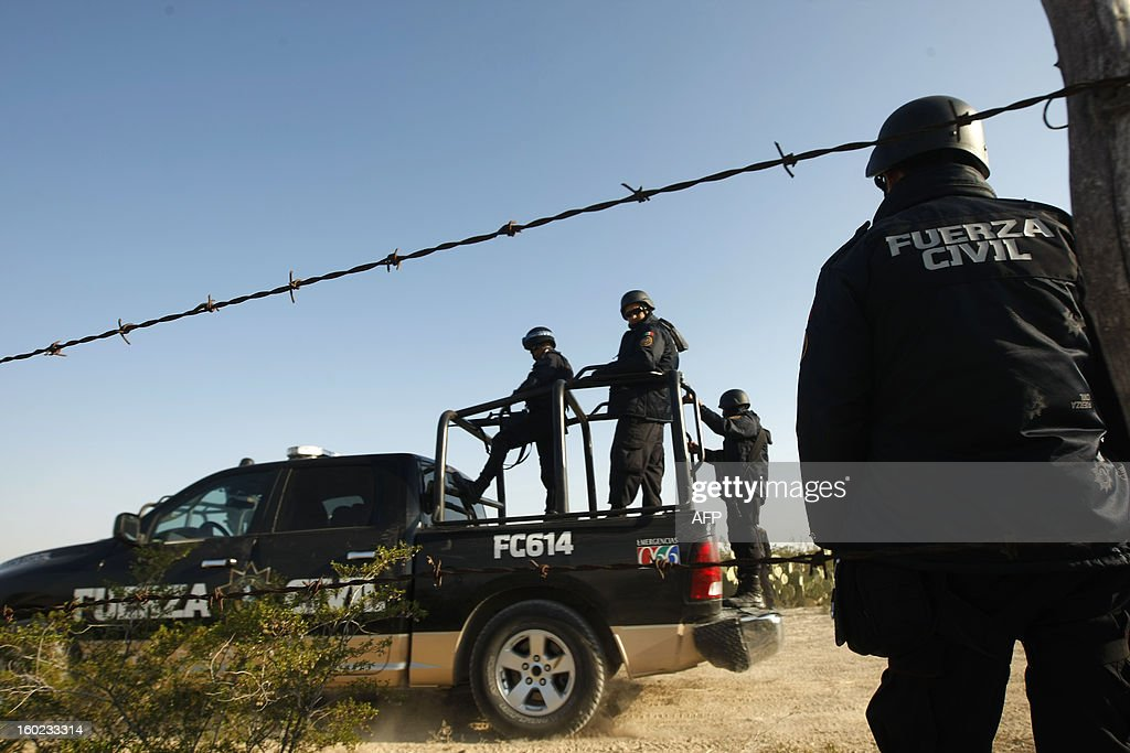 Mexican police stand guard in the site where the bodies of the members of the musical Band Kombo Kolombia were found, in Hidalgo municipality, New Leon state, Mexico on January 28, 2013. At least five corpses have been located in Hidalgo municipality in the north of Mexico, in the same place where last Friday there was brought the disappearance of 20 members of the musical group Kombo Kolombia, they informed this Monday local authorities. In accordance with safety sources of the New Leon State, military men and state police officers located on Sunday night the corpses, which were half-naked, with traces of torture and bullet wounds.