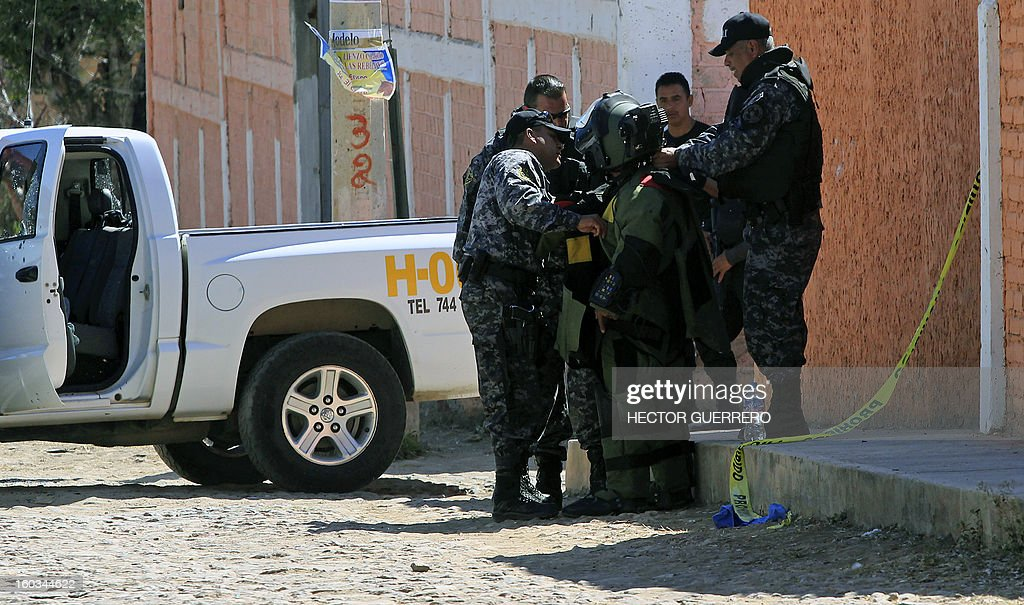 Mexican policemen help a bomb squad member to put on the protective gear before defusing a grenade found at a crime scene in Hostotipaquillo, Jalisco State, Mexico on January 29, 2013. An unidentified armed command killed three people, including the police director of the municipality Hostotipquillo, Lucio Rosales Astorga. AFP PHOTO/Hector Guerrero