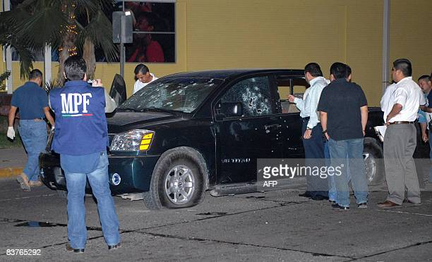 Mexican policemen inspect on November 19 a pickup truck with five policemen dead in Culiacan Sinaloa state northern Mexico The war of drug cartels in...