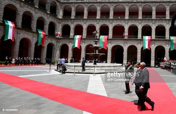Mexican President Enrique Pena Nieto accompanies his Portuguese counterpart Marcelo Rebelo de Sousa during a reception ceremony at the Palacio...