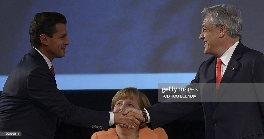 Mexican President Enrique Pena Nieto (L) and Chilean President Sebastian Pinera shake hands as German Chancellor Angela Merkel looks on during the IV Business Meeting being held in Santiago in the framework of the Community of Latin American and Caribbean States (CELAC)-European Union (EU) Summit, on January 26, 2013. Latin American and European leaders open a two-day summit here in Chile on Saturday to give a fresh impetus to efforts to seal a free trade agreement between their two blocs. AFP PHOTO / RODRIGO BUENDIA