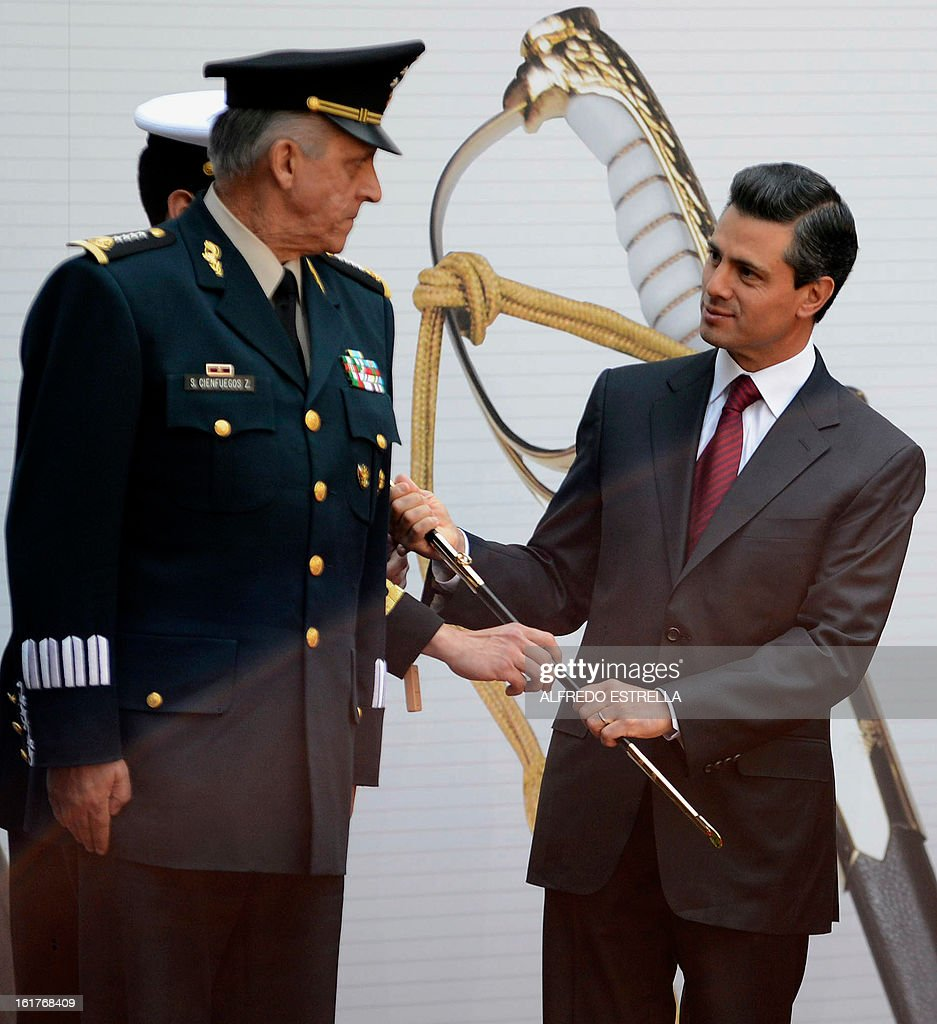 Mexican President Enrique Pena Nieto (R), and Defence Secretary General Salvador Cienfuegos take part in the ceremony known as the 'Delivery of the Sword and Sabre to the President of Mexico and Supreme Commander of the Armed Forces', at the National Palace in Mexico City, on February 15, 2013. AFP PHOTO/Alfredo ESTRELLA