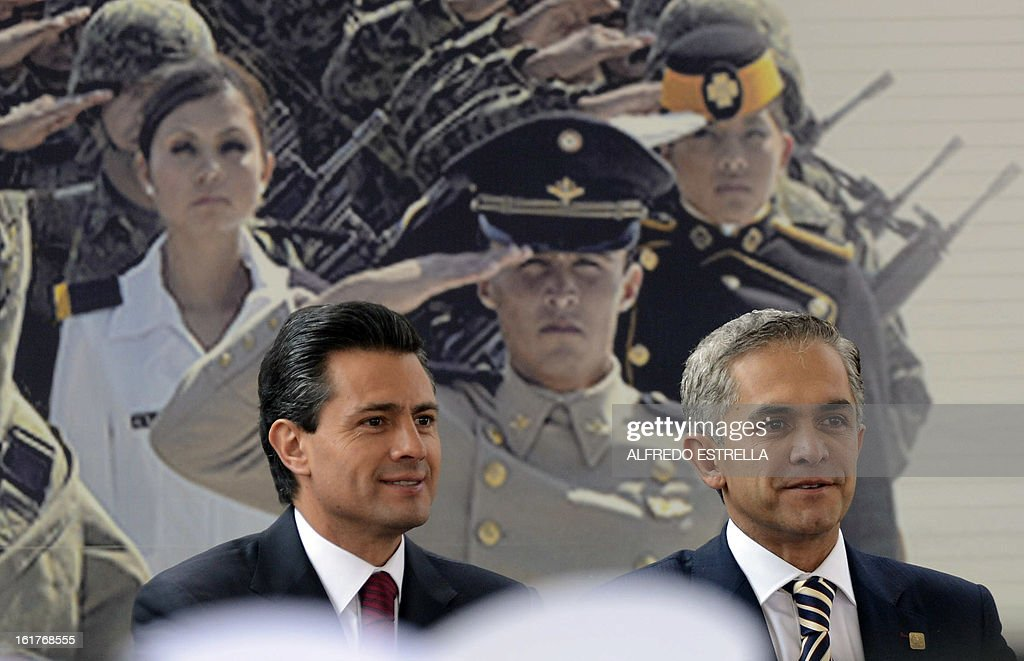 Mexican President Enrique Pena Nieto (L) and Mexico City's Mayor Miguel Angel Mancera attend the opening of the exhibition 'Armed Forces, Pride for Serving Mexico' at Zocalo Square in Mexico City, following a cweremony involving the Armed Foreces, on February 15, 2013. AFP PHOTO/Alfredo ESTRELLA