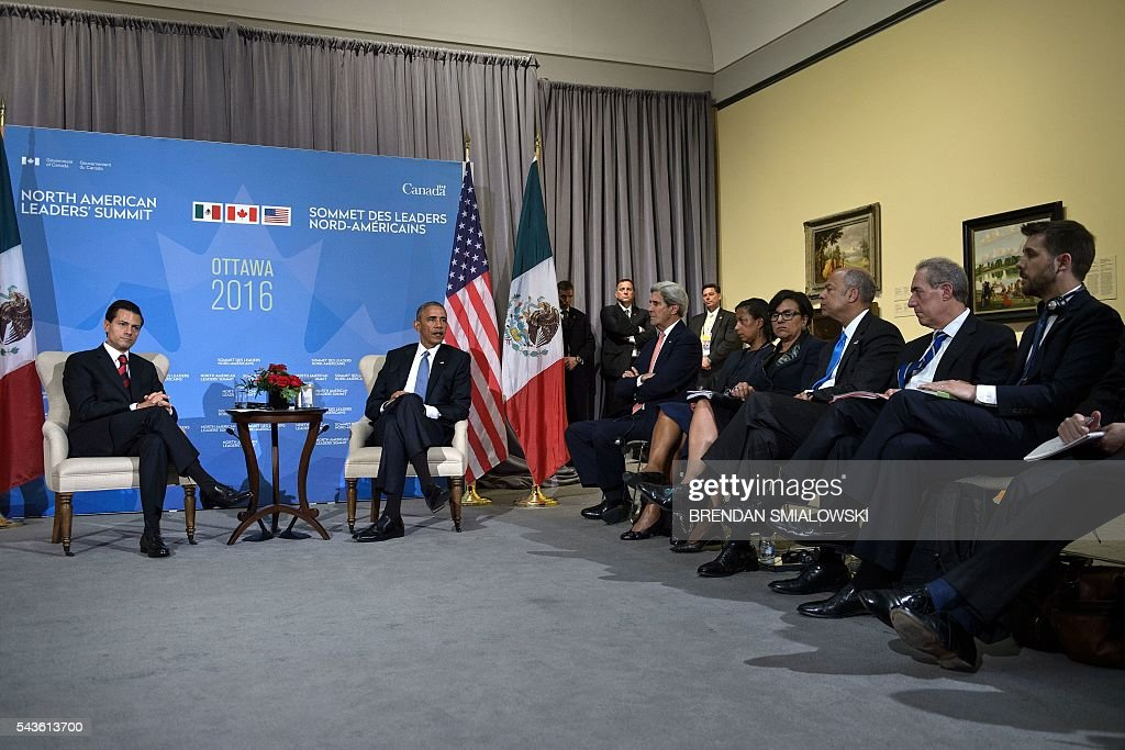 Mexican President Enrique Pena Nieto (L) and US President Barack Obama wait with others after a meeting during the North American Leaders Summit at the National Gallery of Canada on June 29, 2016 in Ottawa, Ontario. / AFP / Brendan Smialowski
