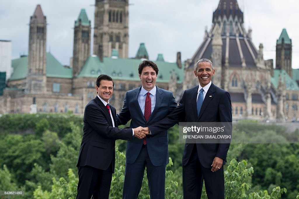 Mexican President Enrique Pena Nieto, Canadian Prime Minister Justin Trudeau and US President Barack Obama pose for a group photo with Canada's Parliament Hill in the background during the North American Leaders Summit on June 29, 2016 in Ottawa, Ontario. / AFP / Brendan Smialowski