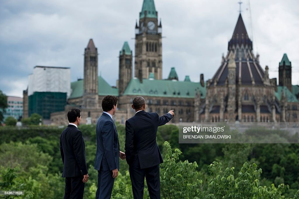 Mexican President Enrique Pena Nieto, Canadian Prime Minister Justin Trudeau and US President Barack Obama look at Canada's Parliament Hill after a group photo during the North American Leaders Summit on June 29, 2016 in Ottawa, Ontario. / AFP / Brendan Smialowski