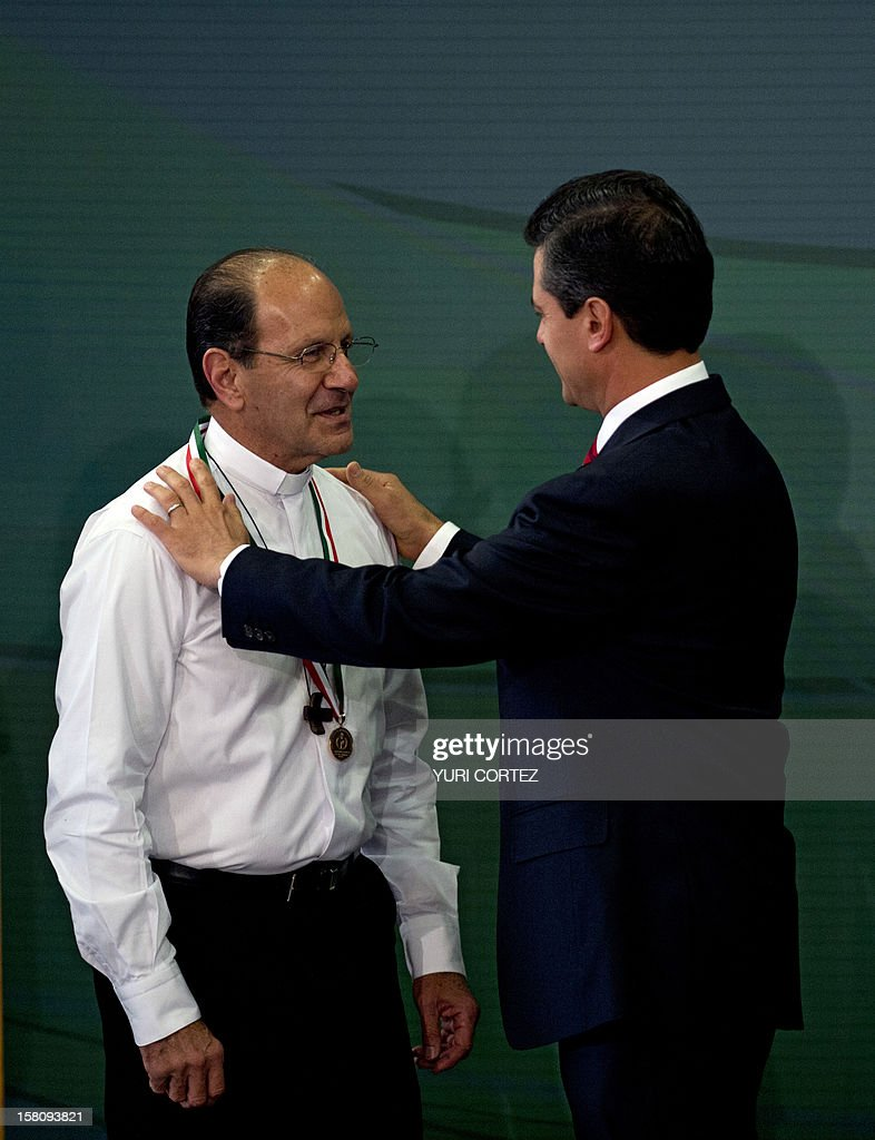 Mexican President, Enrique Pena Nieto (R), decorates Mexican Catholic priest Alejandro Solalinde (L) with the National Human Rights Award during a ceremony at Los Pinos Presidential Palace in Mexico City on December 10, 2012. Solalinde is the founder and director of 'Brothers on the Road' shelter in Oaxaca, Mexico, which dedicates to defend the rights of migrants, receiving some 200 per day. AFP PHOTO/ YURI CORTEZ
