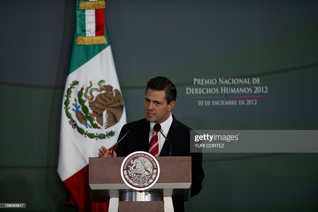 Mexican President, Enrique Pena Nieto delivers a speech during a ceremony in which he decorated Mexican Catholic priest Alejandro Solalinde (out of frame) with the National Human Rights Award at Los Pinos Presidential Palace in Mexico City on December 10, 2012. Solalinde is the founder and director of 'Brothers on the Road' shelter in Oaxaca, Mexico, which dedicates to defend the rights of migrants, receiving some 200 per day.