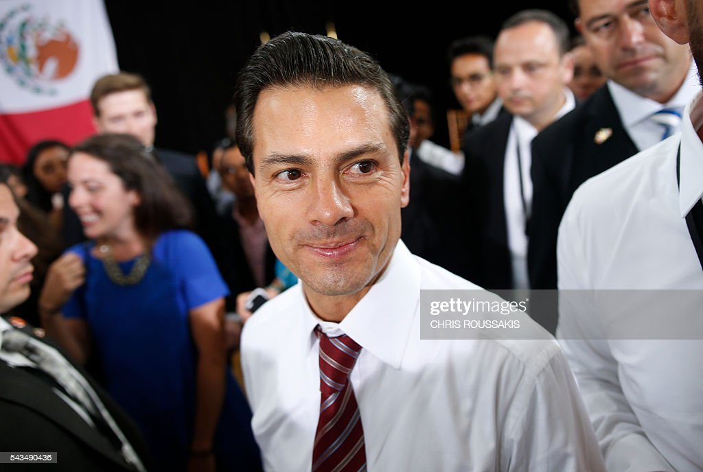Mexican President Enrique Pena Nieto exits through a crowd of people after participating in a youth question and answer session ahead of the 'Three Amigos Summit' in Ottawa, June 28, 2016. Canadian Prime Minister Justin Trudeau and his guests US President Barack Obama and Mexican President Enrique Pena Nieto will meet in Ottawa for the North American Leaders Summit June 29 morning under a climate of economic uncertainty following Britain's vote to leave the European Union. / AFP / Chris Roussakis
