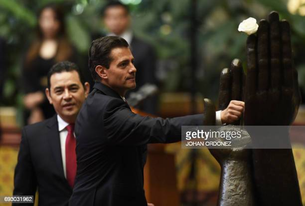 Mexican President Enrique Pena Nieto takes part in the 'Peace Rose' ceremony next to Guatemalan President Jimmy Morales at the Palace of Culture in...