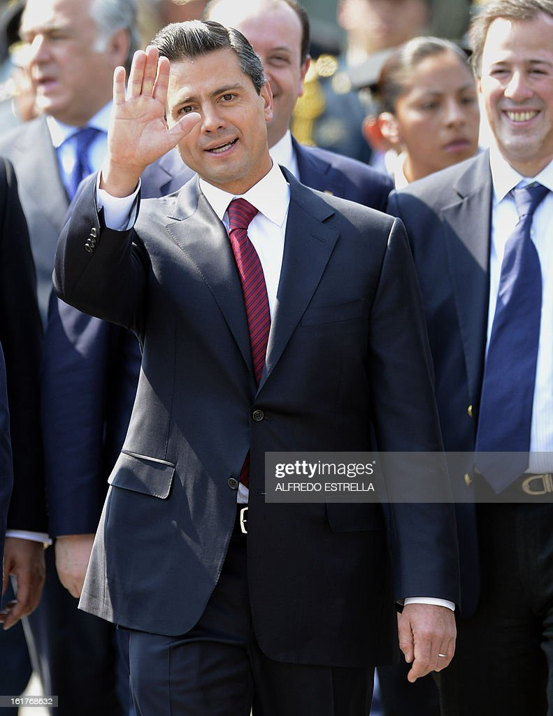 Mexican President Enrique Pena Nieto waves during a tour of the exhibition 'Armed Forces, Pride for Serving Mexico' at Zocalo Square in Mexico City, following a ceremony involving the Armed Foreces, on February 15, 2013. AFP PHOTO/Alfredo ESTRELLA