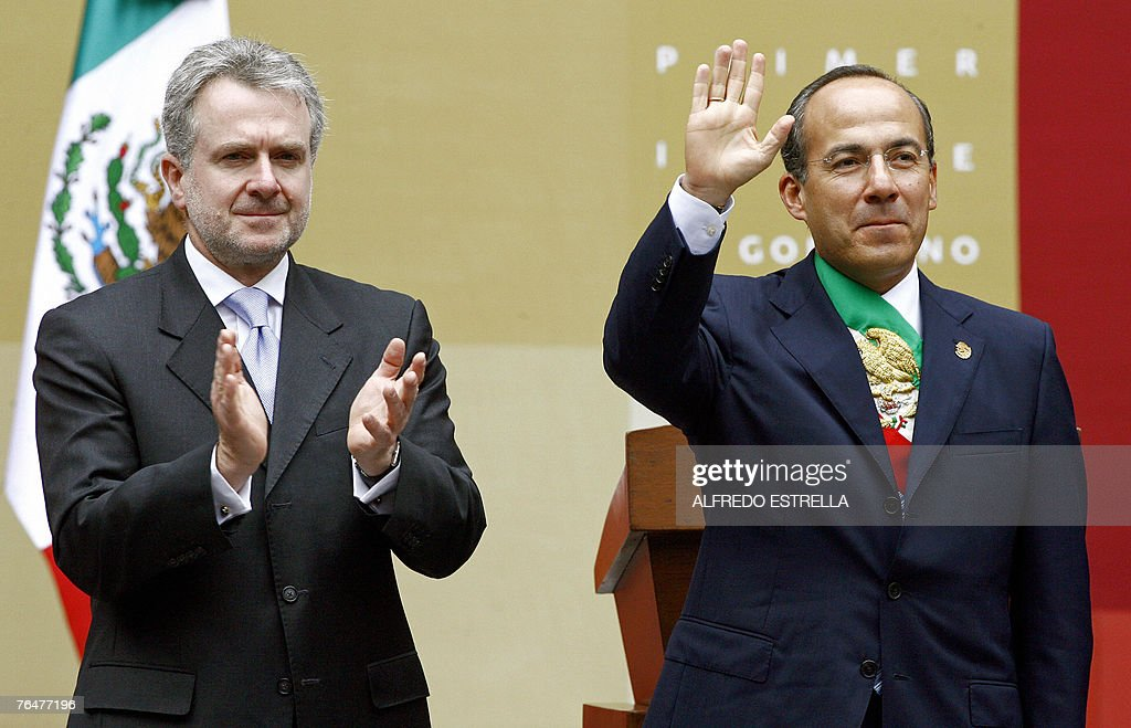 Mexican president Felipe Calderon waves next to PAN's senator Santiago Creel before delivering a speech on his annual report at the National Palace...