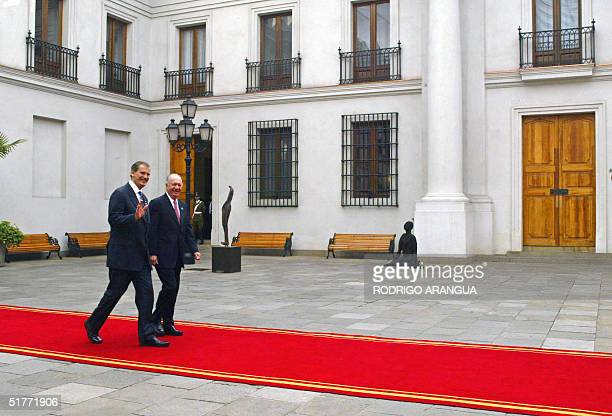 Mexican President Vicente Fox waves next to Chilean President Ricardo Lagos as he enters at La Moneda Presidential Palace to attend the opening of...