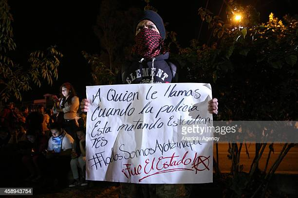 Mexican protestor holds a banner as students demanding justice and live appearance of the 43 students missing in Iguala Guerrero hold a demonstration...
