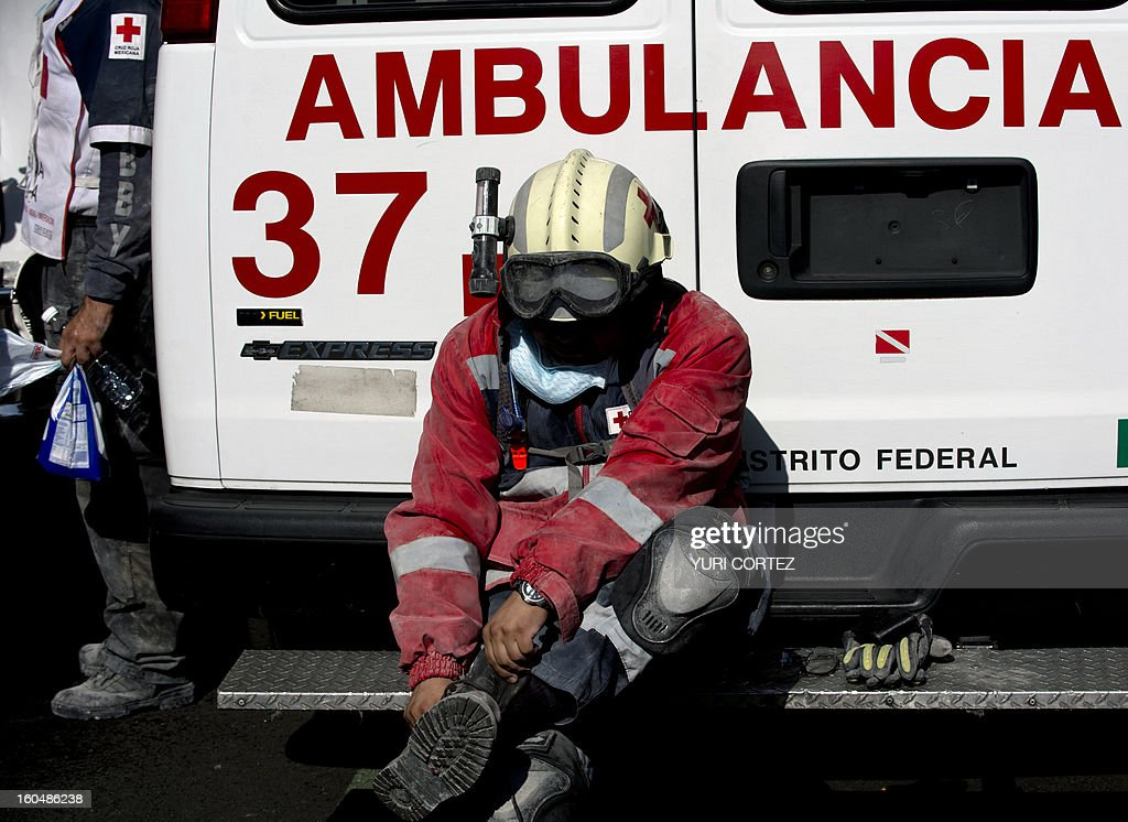 A Mexican Red Cross member takes off his boots during a break on rescue works at the headquarters of state-owned Mexican oil giant Pemex, where a blast took place on the eve, in Mexico City on February 1, 2013. An explosion rocked the skyscraper, leaving up to 32 dead and 121 injured. Hundreds of firefighters, police and soldiers toiled through the night after the blast ripped through an annex of the 54-floor tower also leaving concrete, computers and office furniture strewn on the ground. AFP PHOTO/Yuri CORTEZ