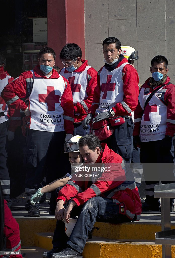 Mexican Red Cross members take a rest during rescue works at the headquarters of state-owned Mexican oil giant Pemex, where a blast took place on the eve, in Mexico City on February 1, 2013. An explosion rocked the skyscraper, leaving up to 32 dead and 121 injured. Hundreds of firefighters, police and soldiers toiled through the night after the blast ripped through an annex of the 54-floor tower also leaving concrete, computers and office furniture strewn on the ground. AFP PHOTO/Yuri CORTEZ