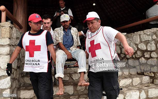 Mexican Red Cross volunteers carry a man during floods in Acapulco Guerrero state Mexico on September 17 2013 The official death toll rose to 47...