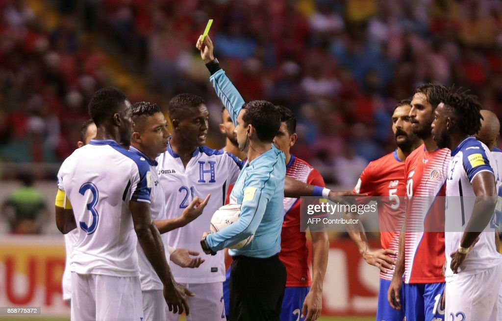 Mexican referee Cesar Ramos shows a yellow card to Honduras' Bryan Acosta(2nd L) during the 2018 World Cup qualifier football match Costa Rica vs Honduras in San Jose on October 7, 2017. / AFP PHOTO / Jorge RENDON