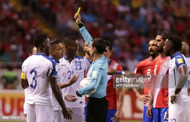 Mexican referee Cesar Ramos shows a yellow card to Honduras' Bryan Acosta during the 2018 World Cup qualifier football match Costa Rica vs Honduras...