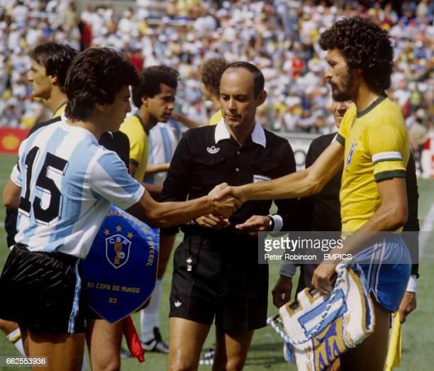 Mexican Referee Mario Rubio Vazquez overseas Argentina Captain Daniel Passarella and Brazil Captain Socrates exchange pennants and shake hands before...