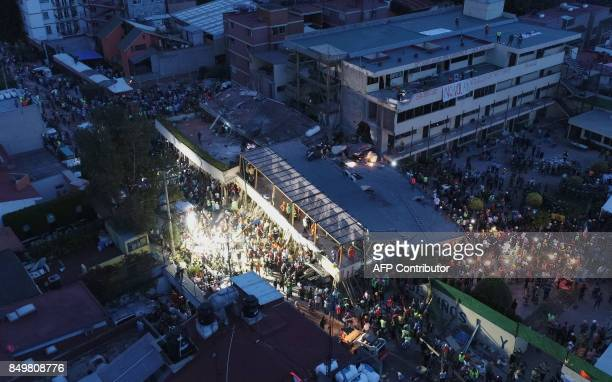 TOPSHOT Mexican rescue teams look for people trapped in the rubble at the Enrique Rebsamen elementary school in Mexico City on September 20 2017 A...