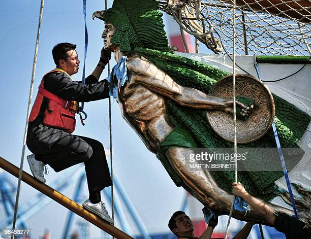 A Mexican sailor cleans the figurehead of sailboat Cuauhtemoc in the port of Valparaiso during the Bicentennial race on April 13 2010 Sailboats from...