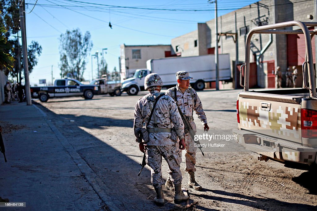 Mexican security officials stand guard outside of a factory where a drug tunnel was discovered leading into the United States on October 31 2013 in...