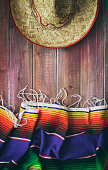 Mexican serape and sombrero on wood