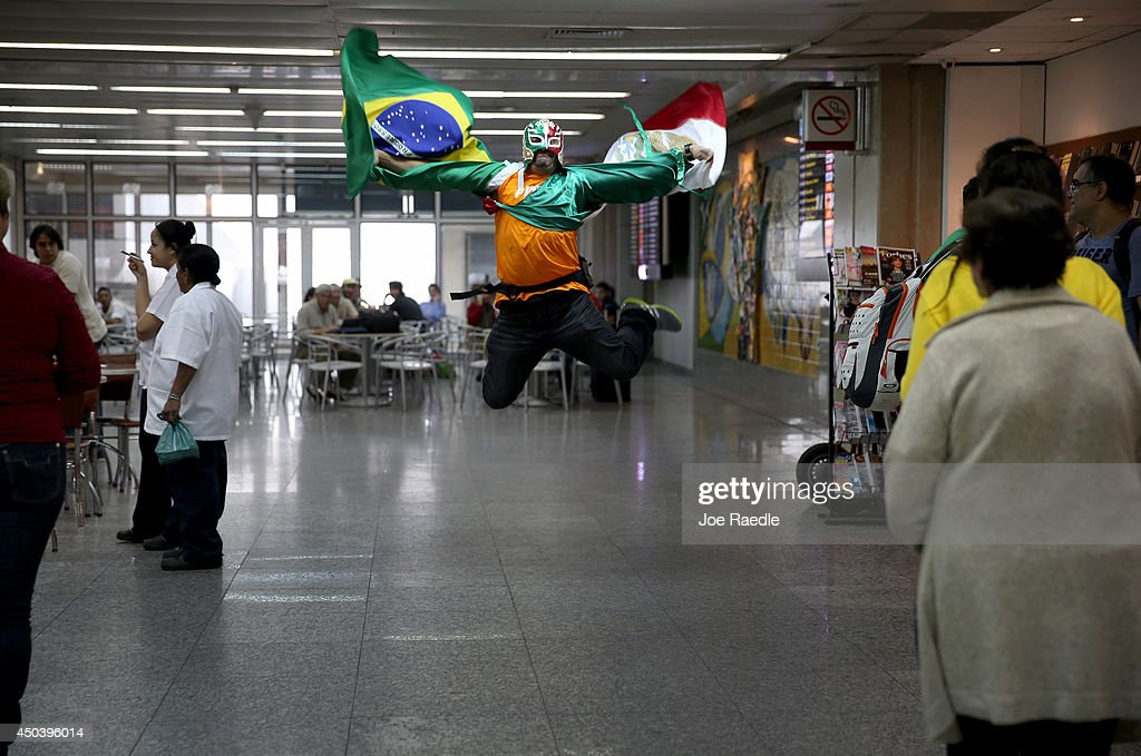 Mexican soccer fan, Herwin Gomez, from Mexico, holds both a Mexican flag and Brazilian as he arrives at the Rio de Janeiro Galeao International Airport for the 2014 FIFA World Cup tournament on June 10, 2014 in Rio de Janeiro, Brazil. Brazil continues to prepare to host the World Cup which starts on June 12th and runs through July 13th.