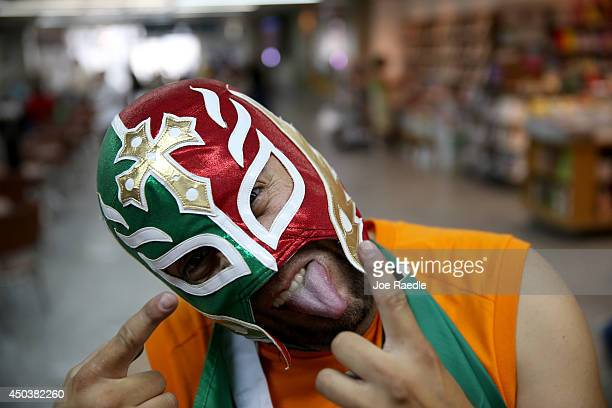 Mexican soccer fan Herwin Gomez from Mexico wears a Lucha libre mask as he arrives at the Rio de Janeiro Galeao International Airport for the World...
