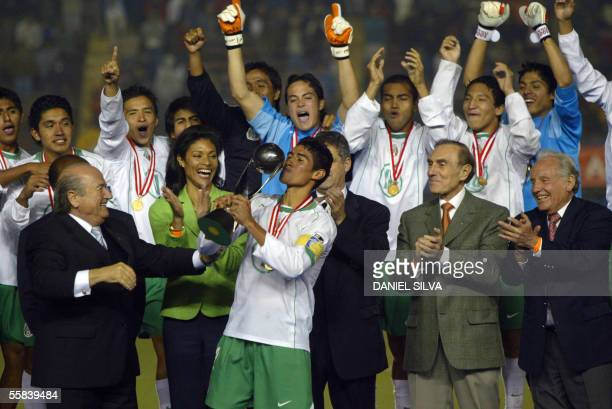 Mexican soccer player Patricio Araujo kisses the FIFA U17 World Cup championship trophy while FIFA's President Joseph Blatter looks on in Lima 02...