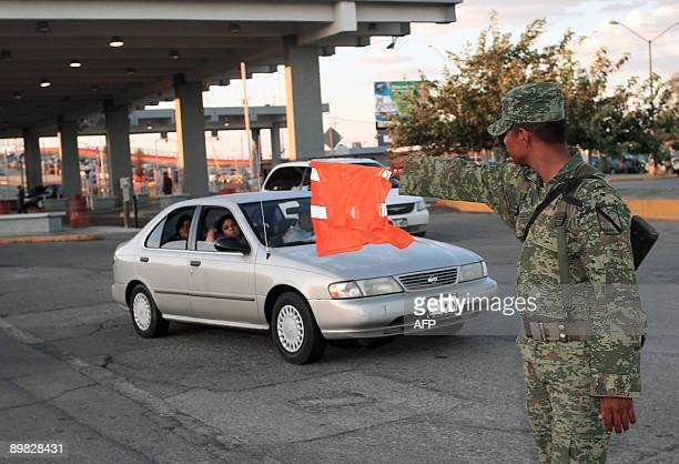 A Mexican soldier controls traffic at the MexicoUS border customs post in Ciudad Juarez on August 16 2009 Mexico's Army took control of customs...