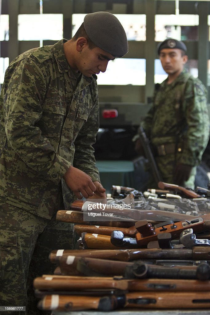 A mexican soldier examines weapons after being exchanged by its owner on January 04, 2013 in Mexico City, Mexico. More than a thousand weapons have been changed for a tablet, bicycles or money in a low-income neighborhood in the capital, according to authorities.