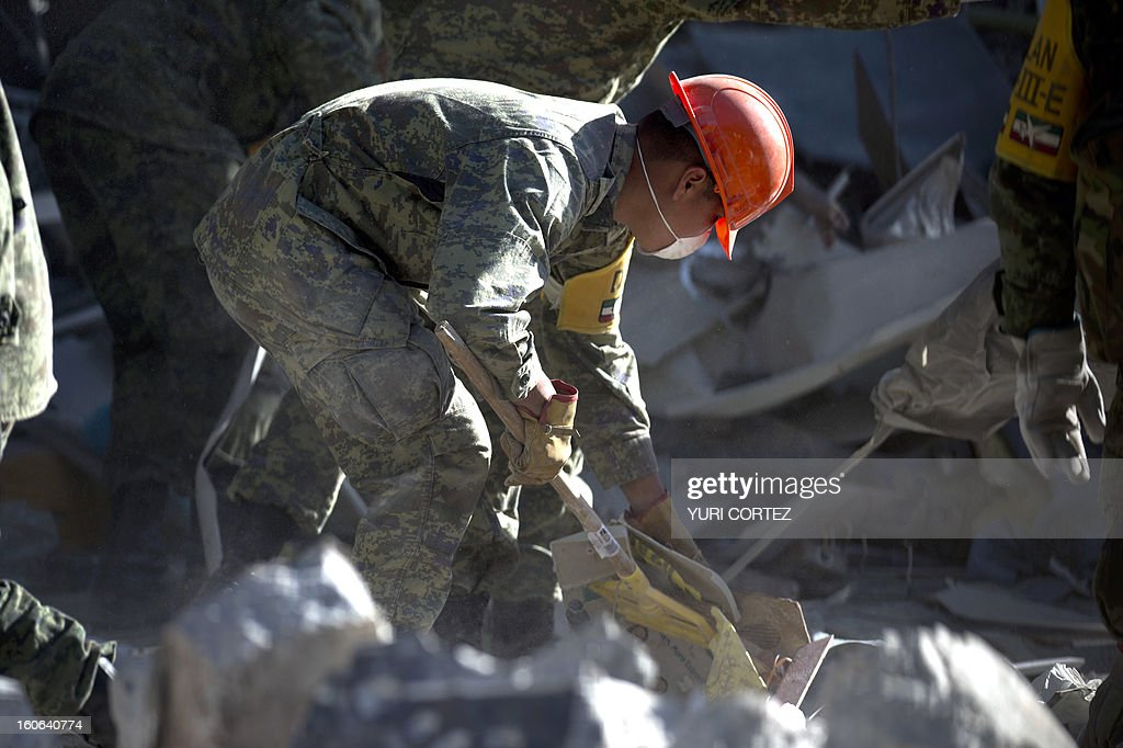 Mexican soldier removes debris at the building of state-owned Mexican oil giant Pemex, in Mexico City on February 4, 2013. An explosion rocked the skyscraper, last week, leaving up to 36 dead and 121 injured. AFP PHOTO/ YURI CORTEZ